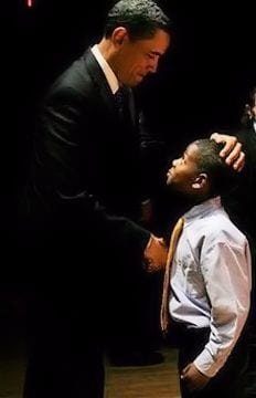 A young black boy shaking hands with President Barack Obama.