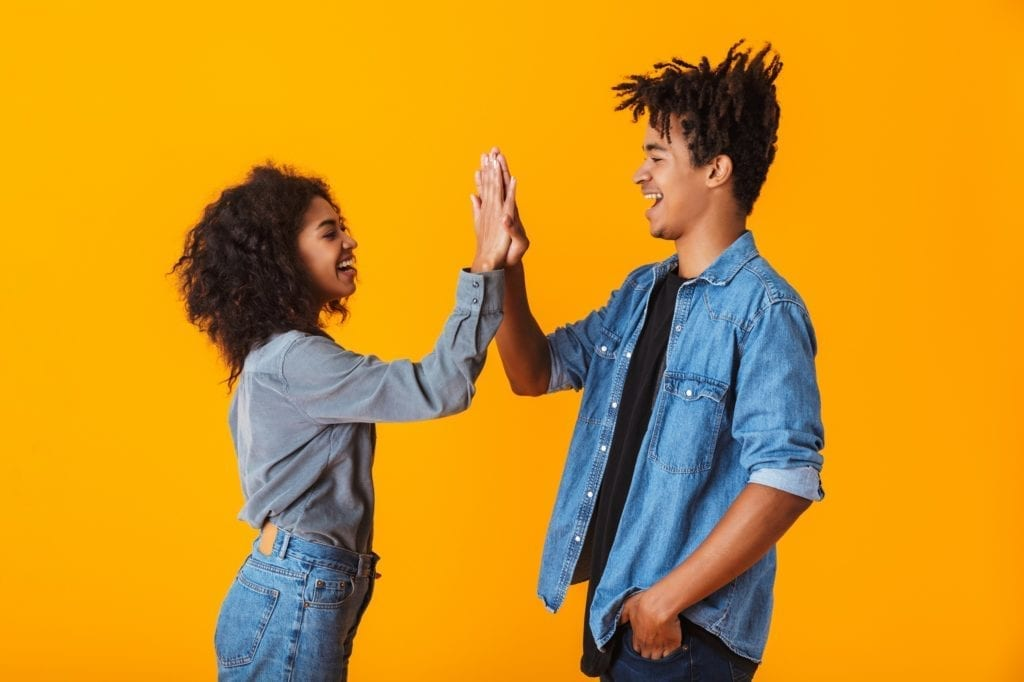 Happy young black couple wearing casual clothes standing isolated over yellow background, giving high five.