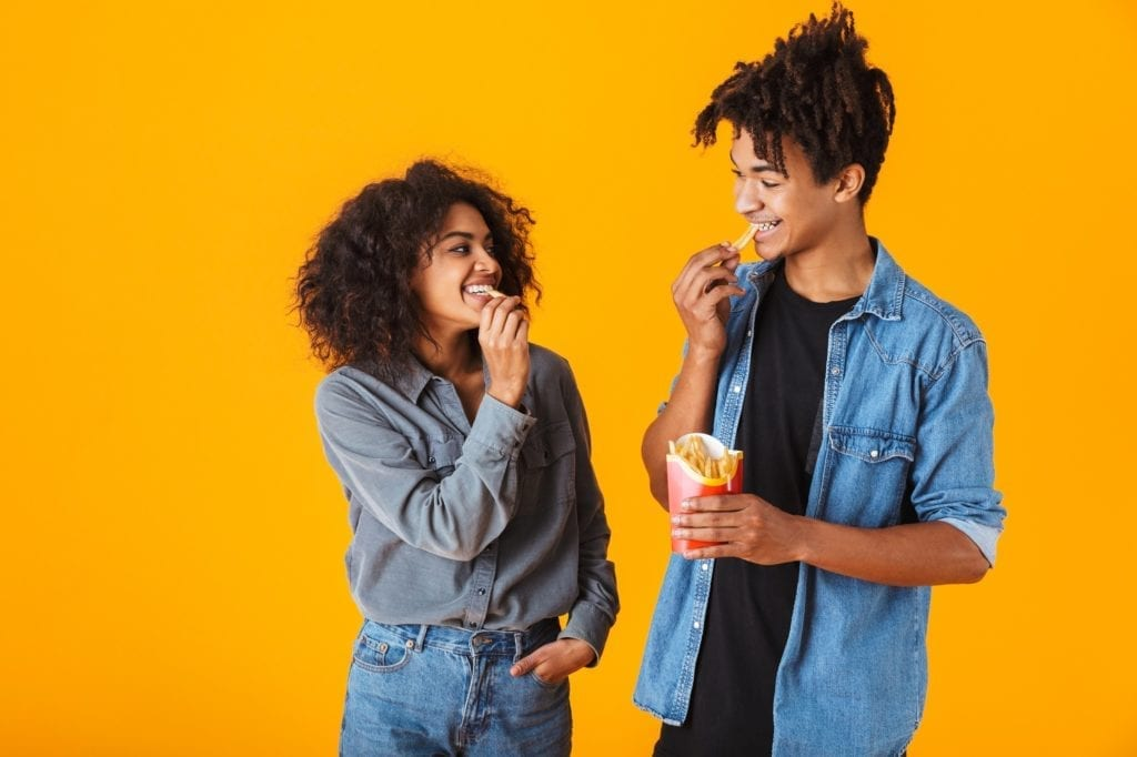 Cheerful young black couple standing isolated over orange background, eating french fries.