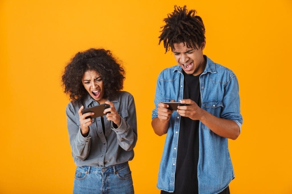 Cheerful young black couple standing isolated over orange background, playing games in mobile phone.