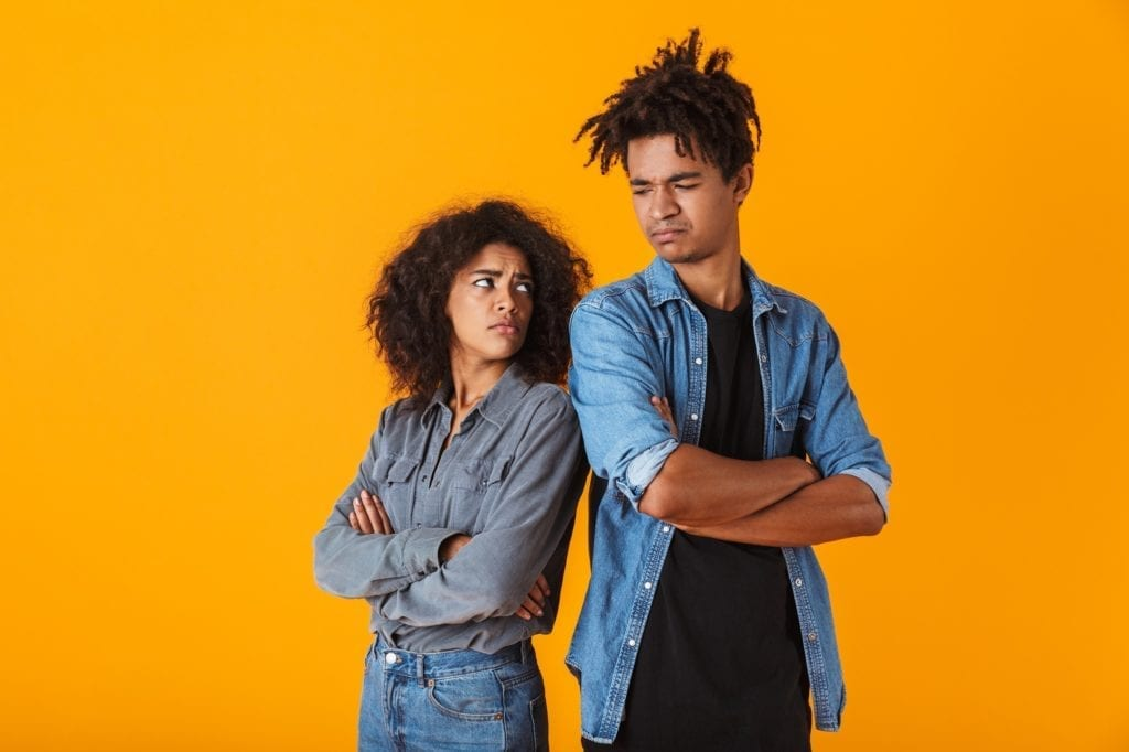 Annoyed looking black couple standing isolated over yellow background, back to back.