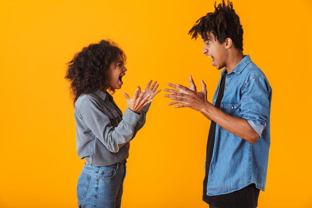 Young black couple standing isolated over yellow background, having an argument.