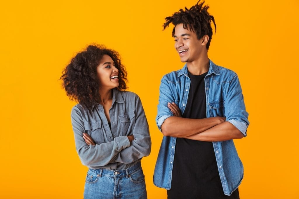 Happy young black couple wearing casual clothes standing isolated over yellow background, arms folded.