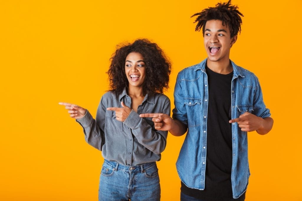 Cheerful young black couple standing isolated over orange background, pointing fingers to the reader's left.