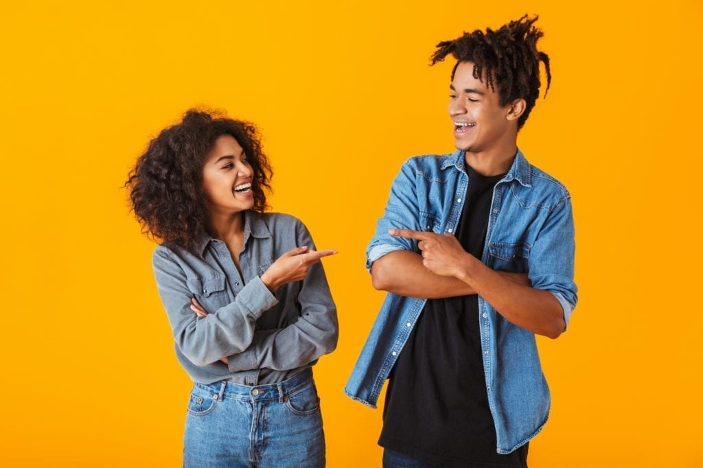 Cheerful young black couple standing isolated over orange background, pointing fingers at each other.