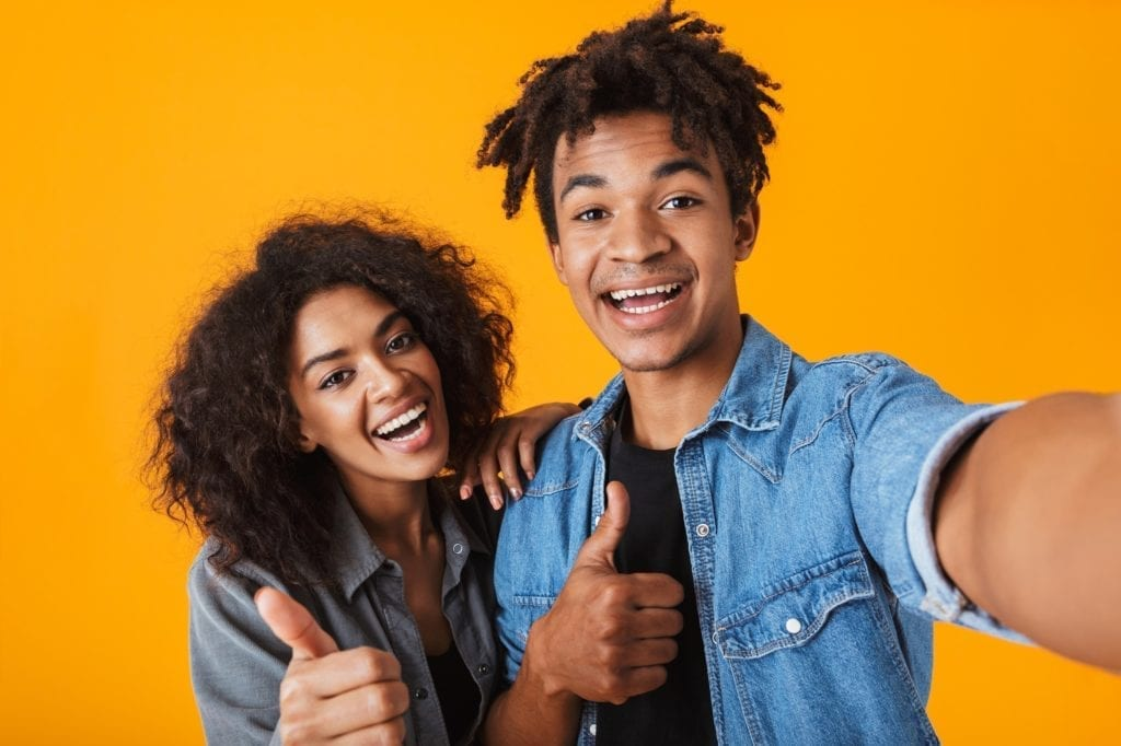 Cheerful young black couple standing isolated over orange background, taking a selfie while both give a thumbs up.