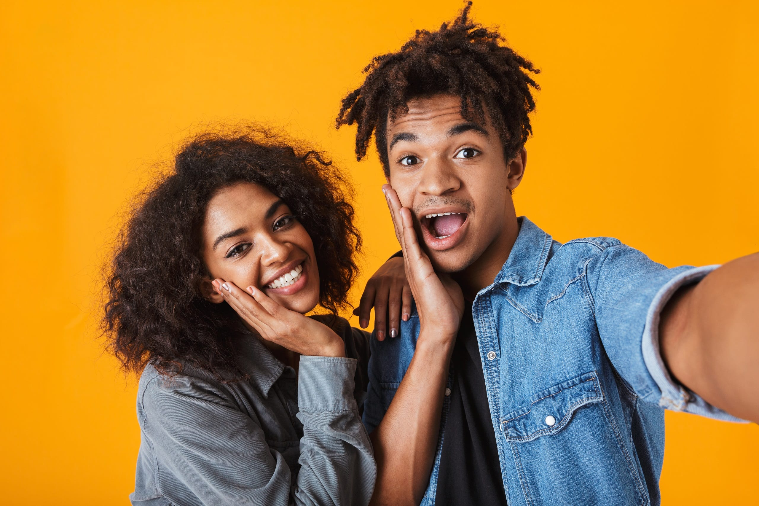 Cheerful young black couple standing isolated over orange background, taking a selfie. Perfect Friendlationship photo.