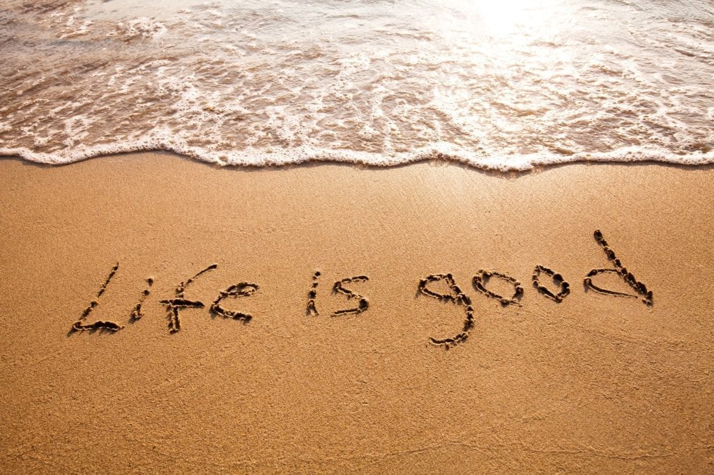 Life is Good written in the sand on a beach.  Water is slowly coming in.