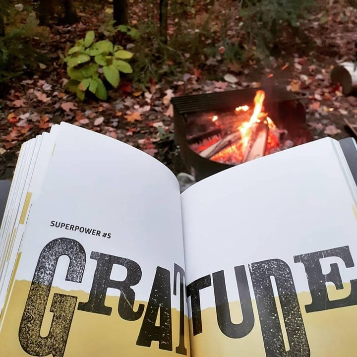 The Life is Good Book open in front of a campfire with a page showing the word Gratitude in type face.
