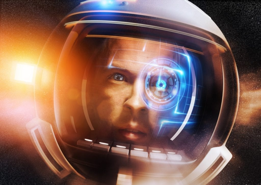 Close-up of a male astronaut in space.  The screen of his helmet is animated with a futuristic digital display.