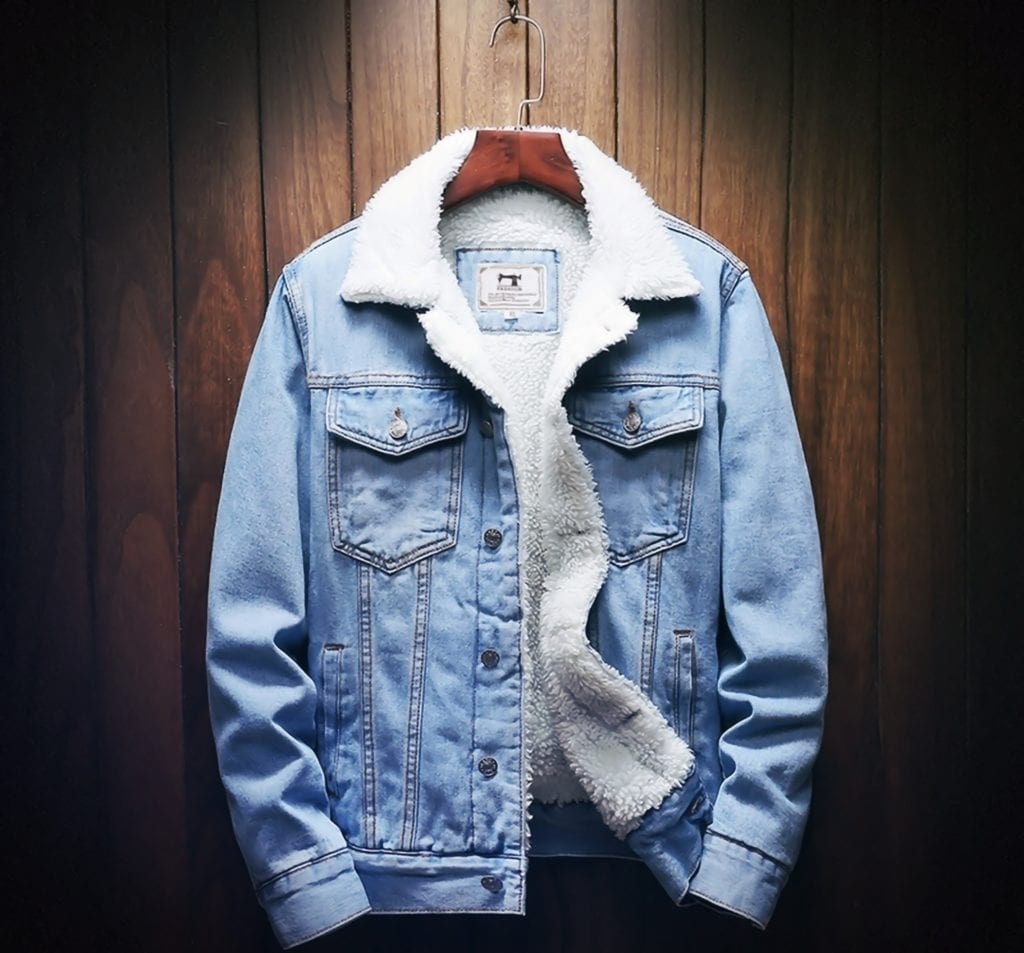 A light blue wool denim jacket on a hanger in from of a wood panel wall.