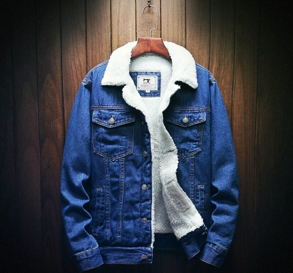 A deep blue wool denim jacket on a hanger in from of a wood panel wall.