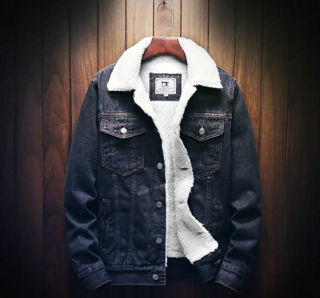 A dark blue wool denim jacket on a hanger in from of a wood panel wall.
