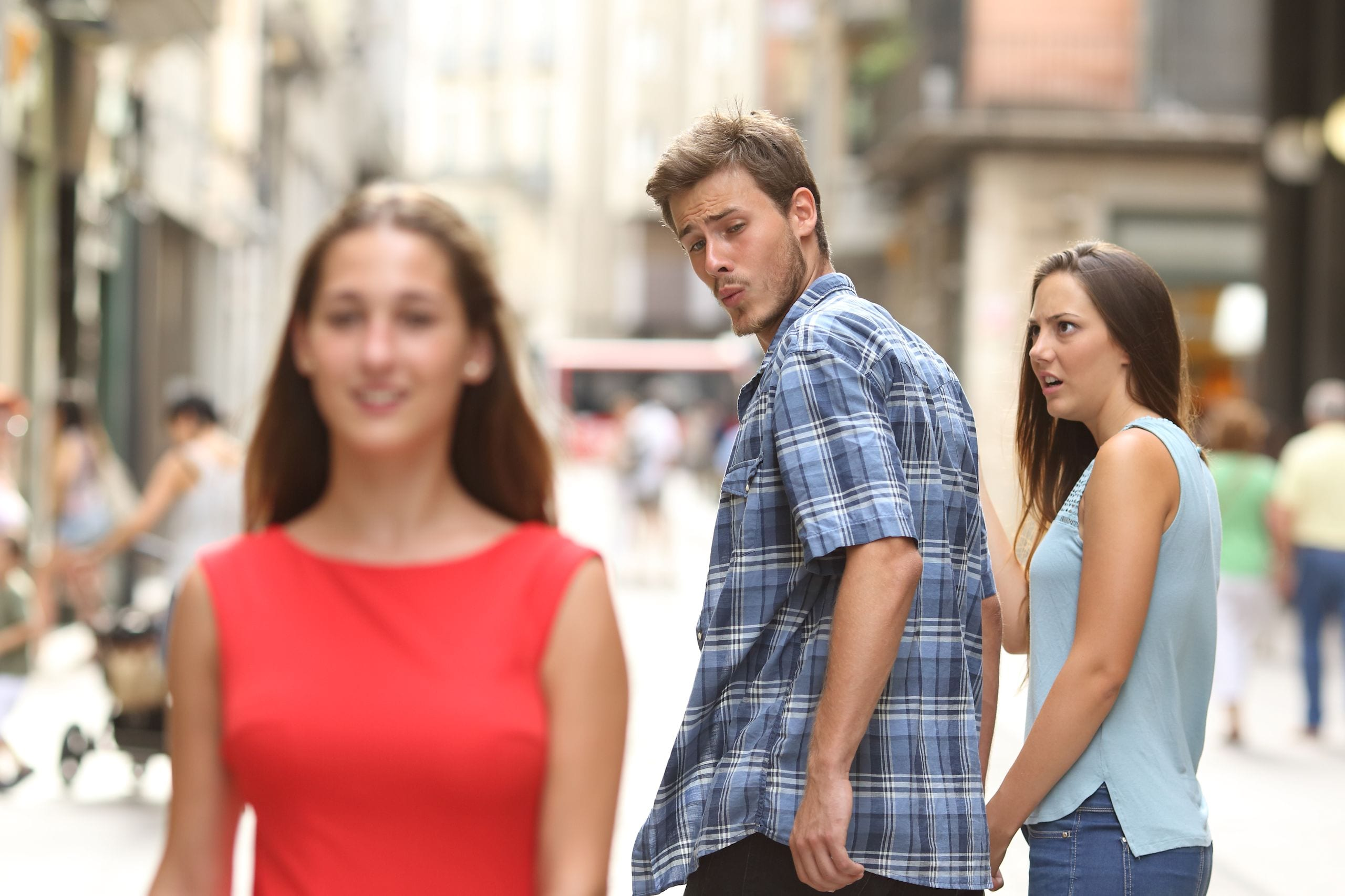 Disloyal man walking with his girlfriend and looking amazed at another seductive girl.