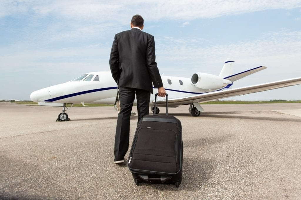 Rear view of businessman with luggage walking towards corporate jet.