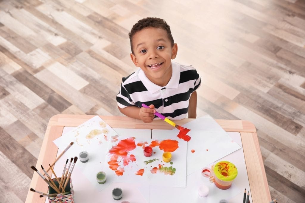 Little African-American boy painting at table indoors.