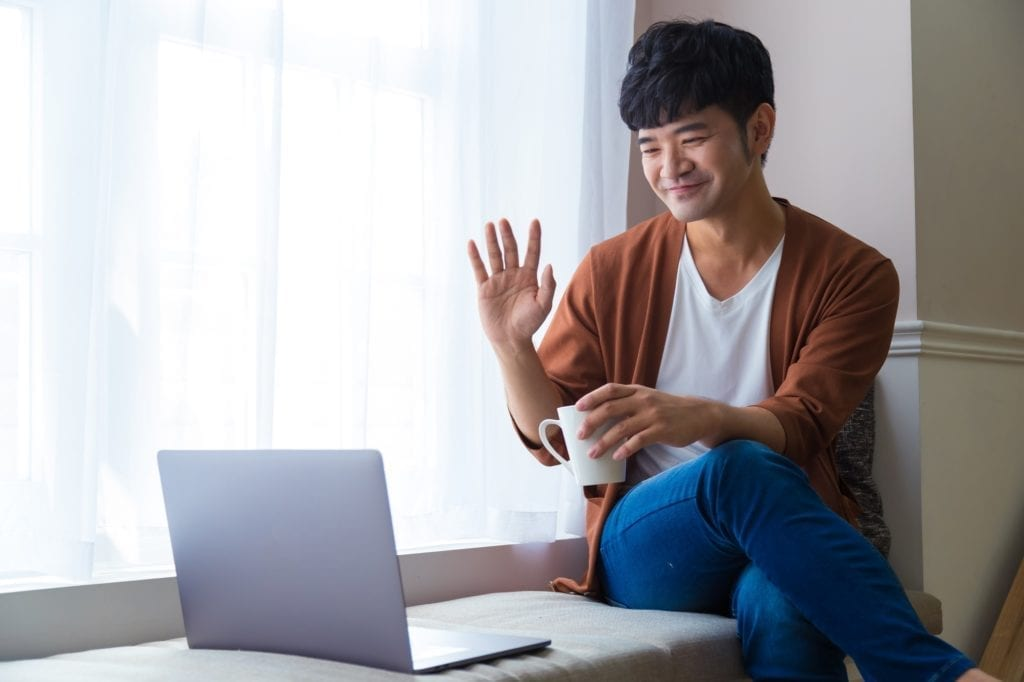 Man talking on video conference online with laptop and sitting near window at home. Talk on video call with friend or relative.