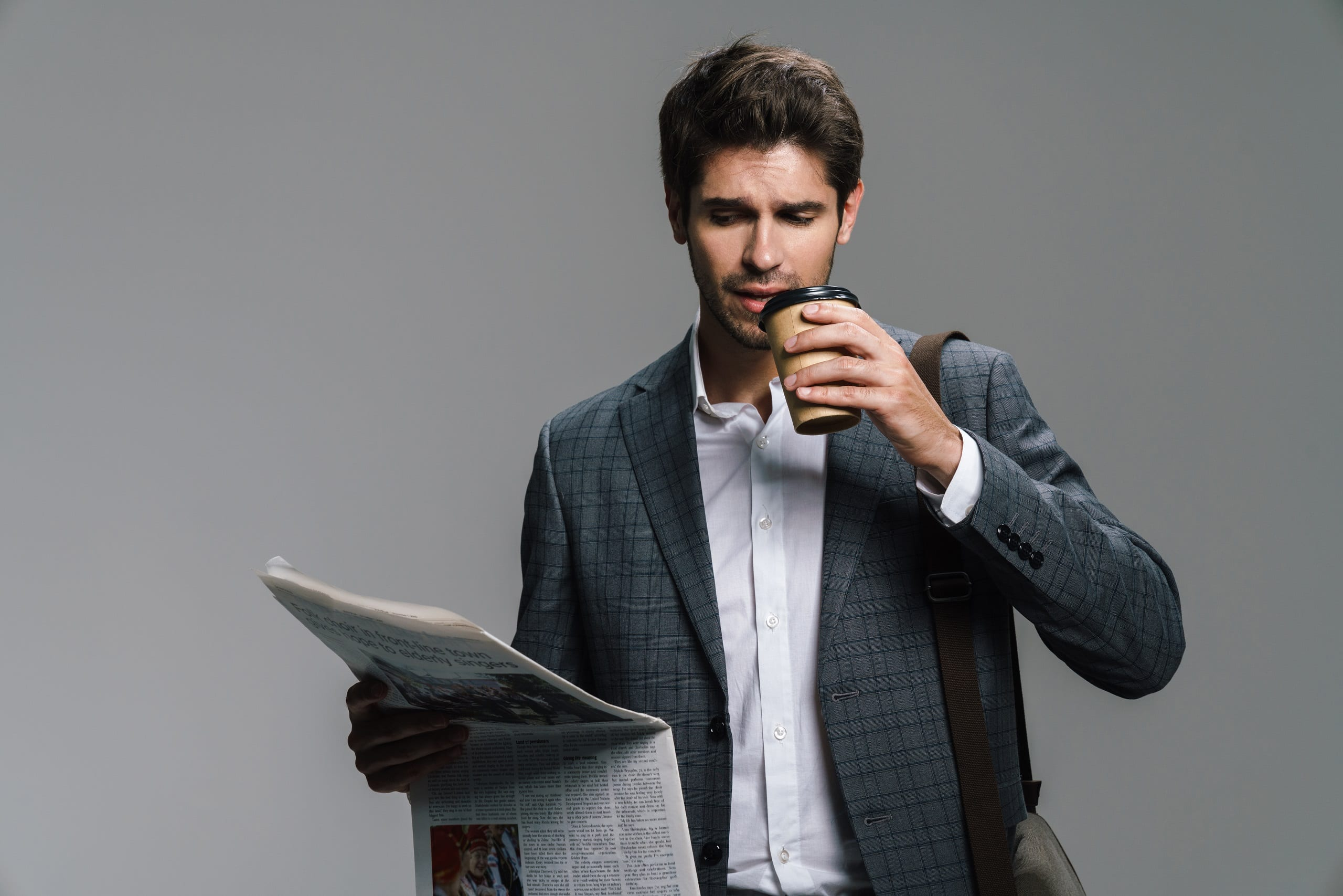 Photo of focused businessman drinking coffee takeaway while reading newspaper isolated over grey wall.