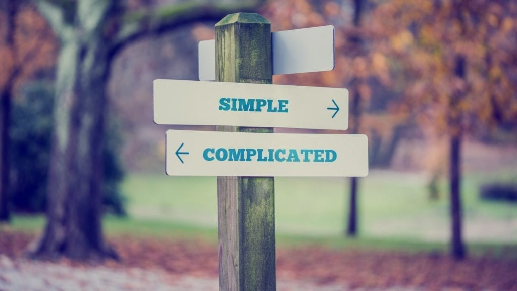 """A picture of a sign post showing one direction leading to """"simple"""" and another leading to """"complicated""""."""