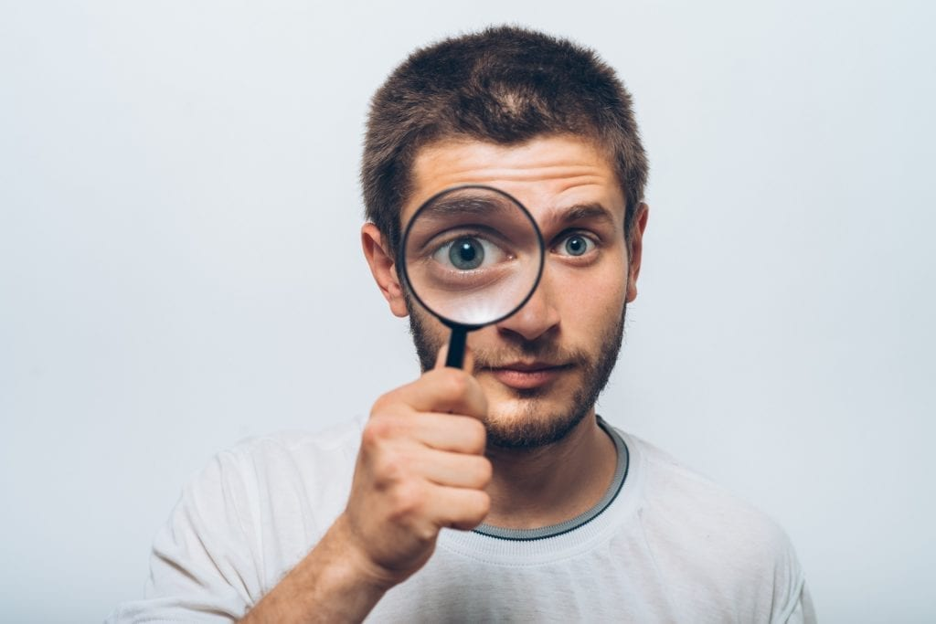 A white male looking through a magnifying glass over a white background.  Denotes Privacy concern.