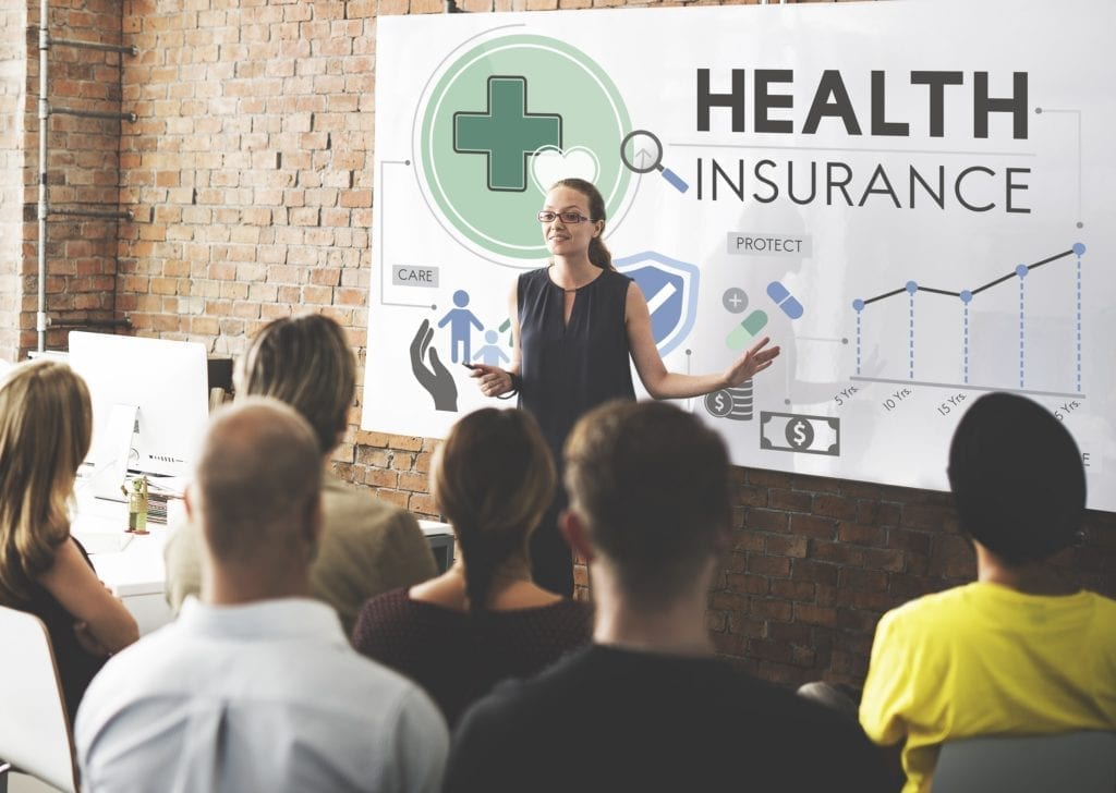 A professional woman giving a presentation to a group about Health Insurance at a business.
