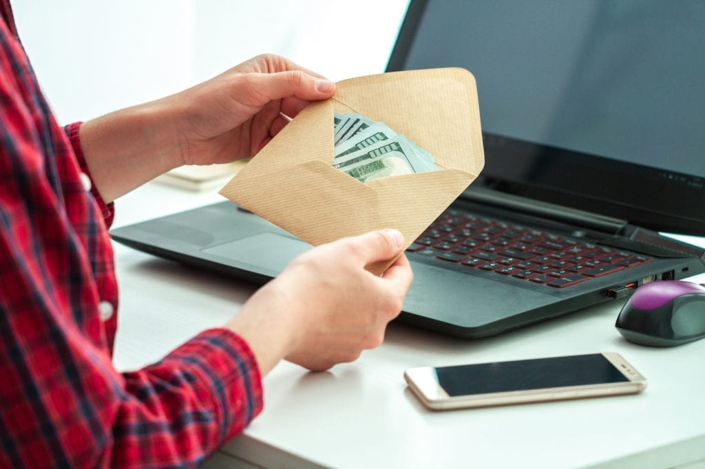 A man holding an envelope of money at his desk while sitting in front of a laptop and a cellphone.