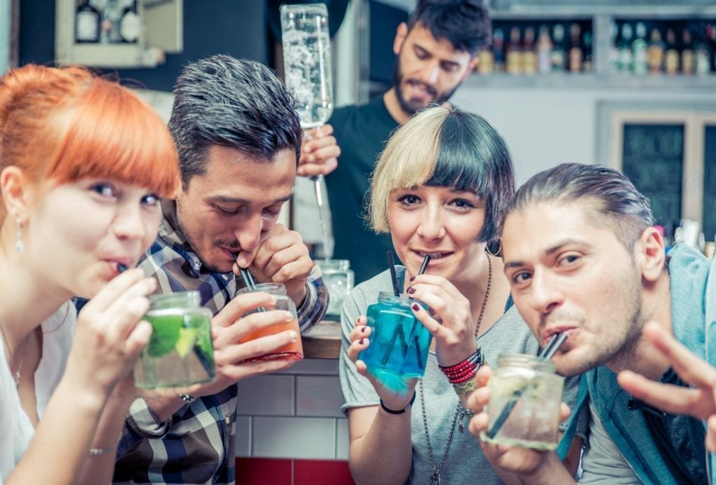 A group of young people having alcoholic drinks while looking into the camera.  The bartender appears to be making another drink in the background.
