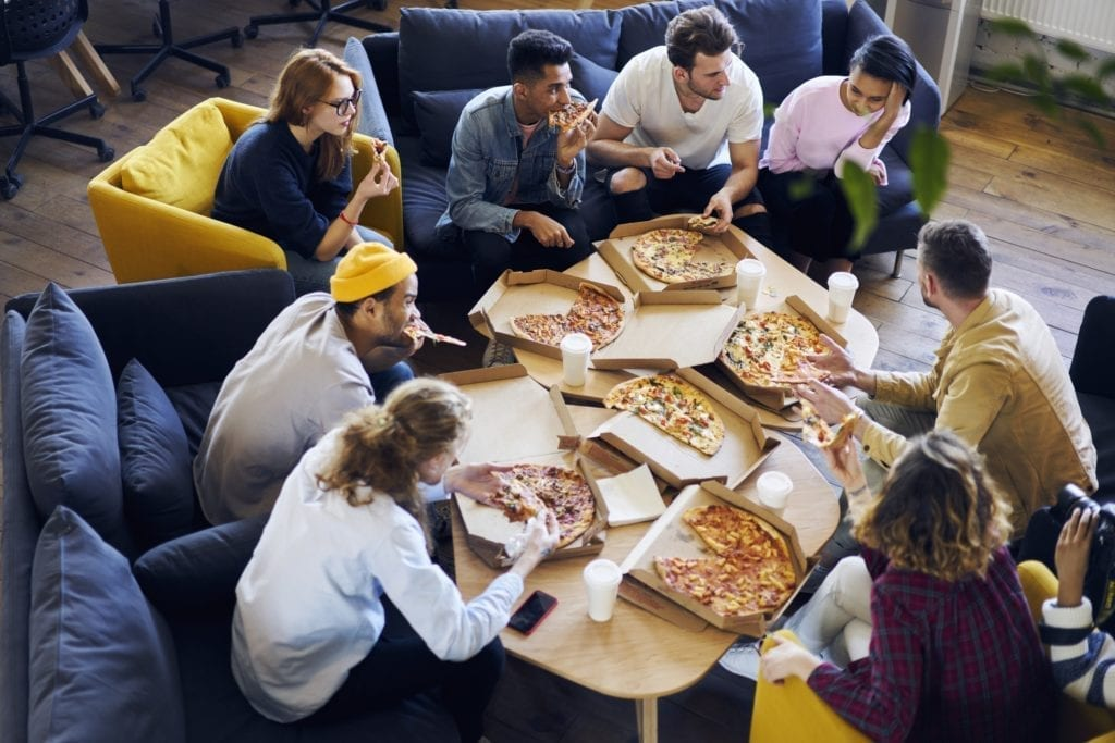 A group of young people eating 6 pizzas together.  Symbolizes getting free food at work.
