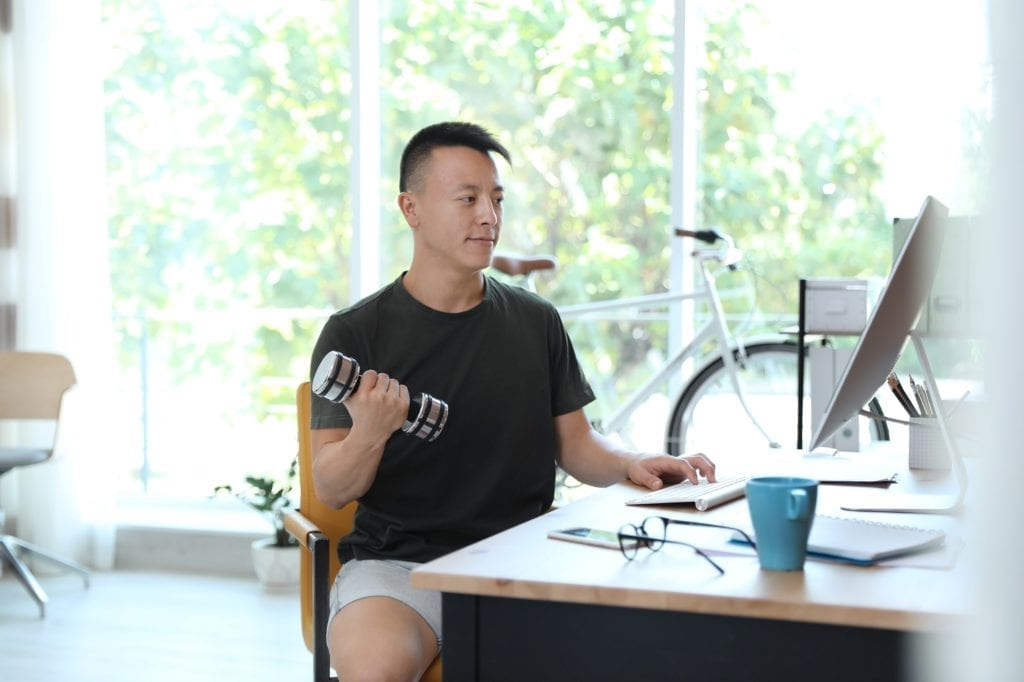 A young Asian businessman wearing athletic clothing sitting at his desk working while lifting a dumbbell.