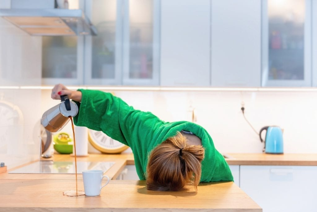 A tired woman in a green robe pouring coffee, but missing her mug and making a mess on her kitchen counter while her head is lying down directly on the counter top in her kitchen.
