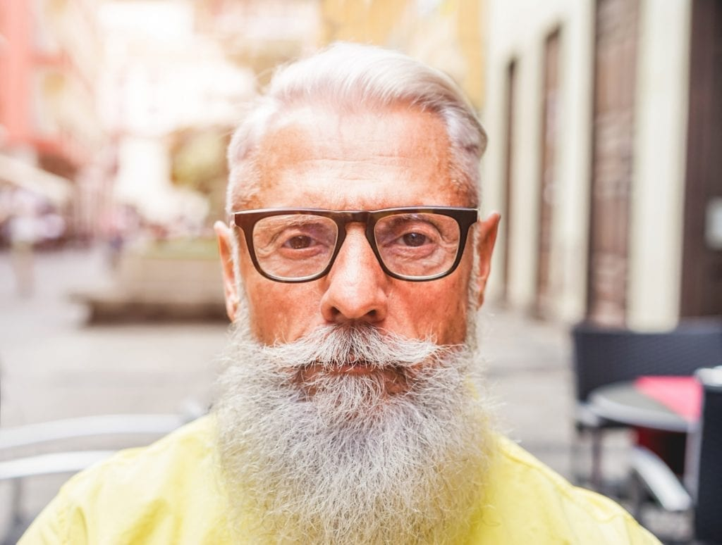 Older man with beard and glasses staring at the camera.  Does he have low confidence?