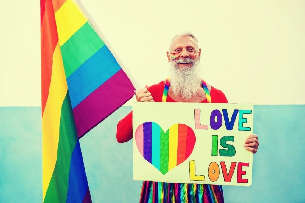 Old man with beard wearing gay pride clothing and holding a sign that says love is love.