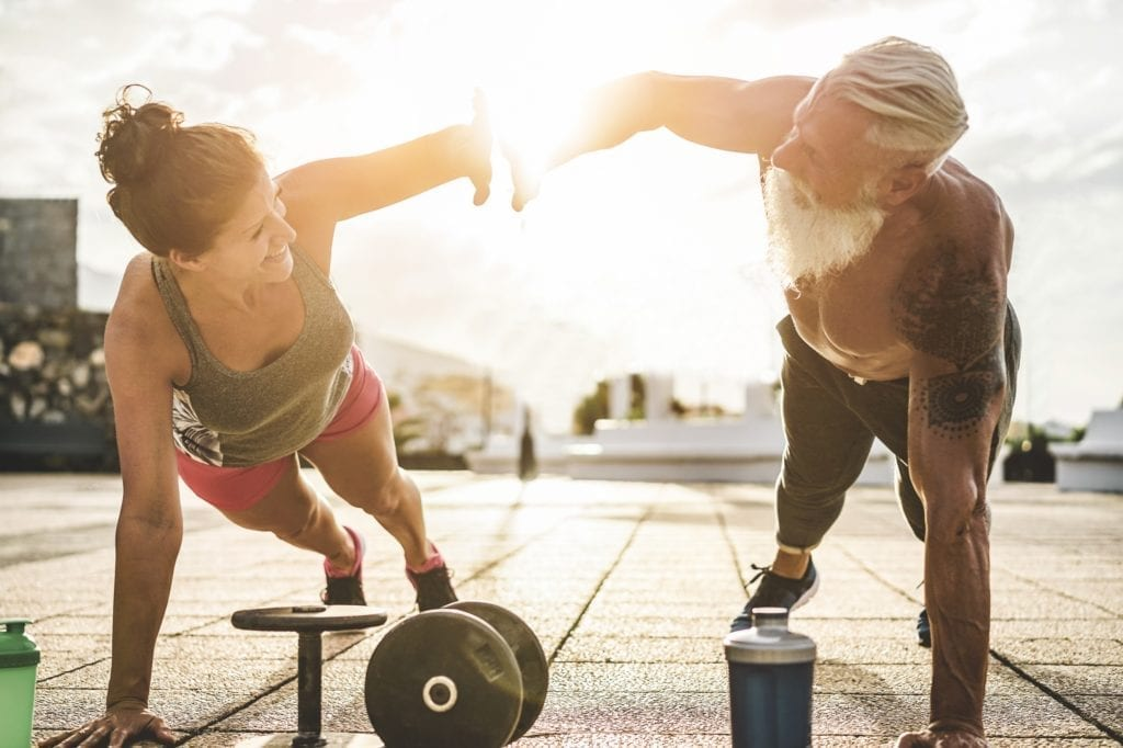Confident old man and younger woman working out together giving each other a five while in the plank position next to some dumbbells.