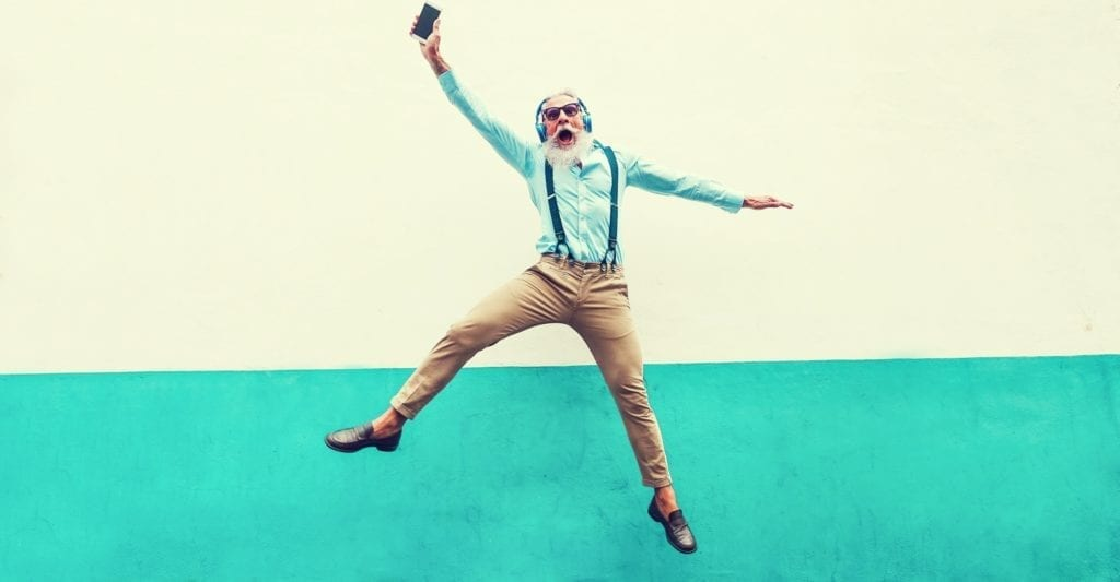 A happy old hipster man jumping into the sky while wearing headphones and holding his cell phone.