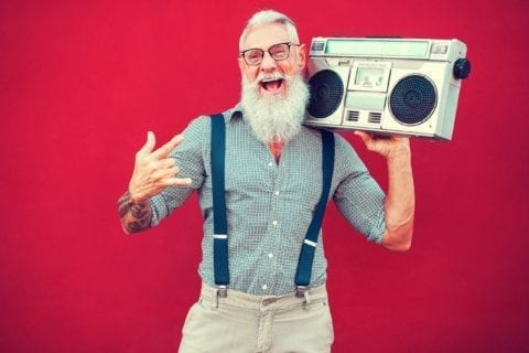 An old hipster man with lots of confidence dancing while holding a boombox on his shoulder. He is wearing suspenders and has a large beard. Standing in front of a red background.