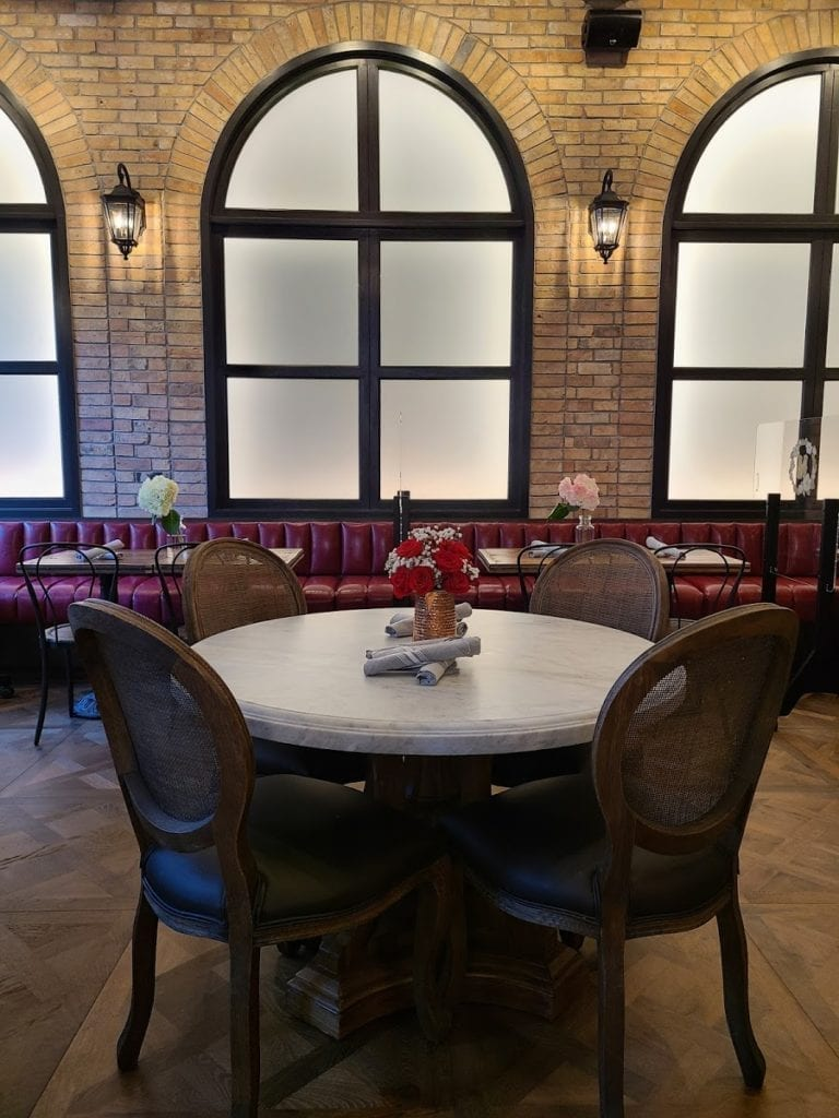 Booth seats and arched windows in the upper-level of Sisters in Alexandria.