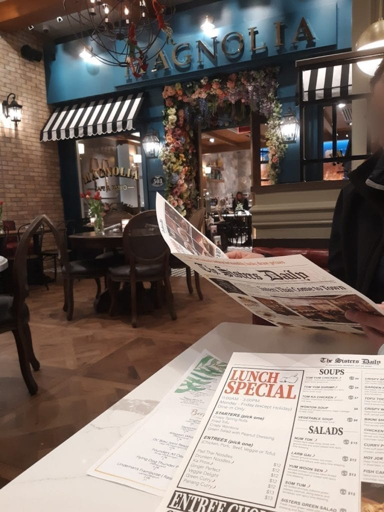 A person reading the menu at Sisters Thai in Alexandria.