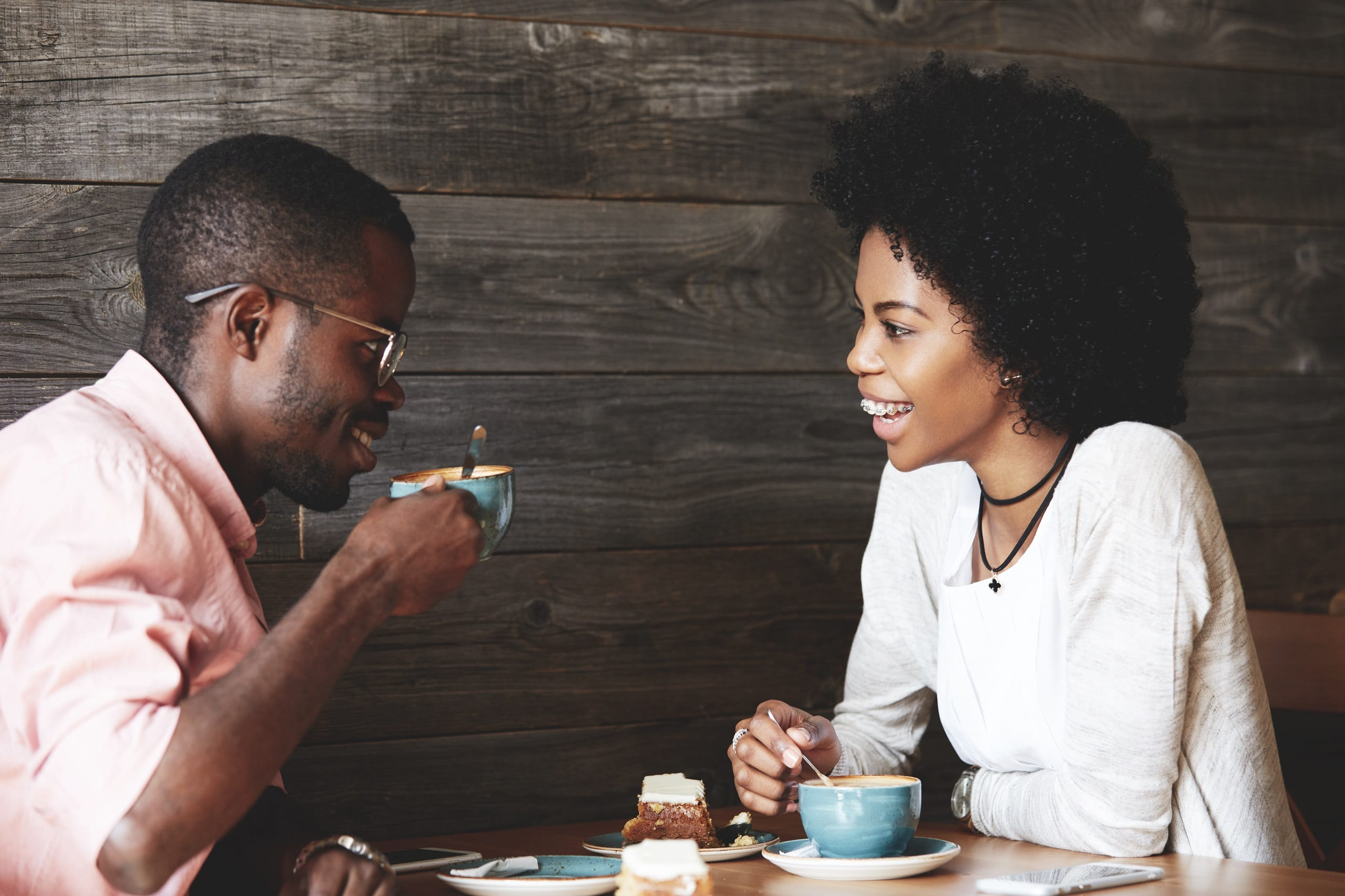 Happy stylish Black friends having coffee together, sitting at a cafe, laughing and having a great time together.
