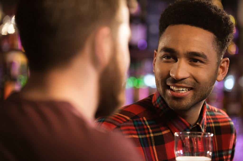 Close up of a two happy male friends drinking beer at bar or pub.