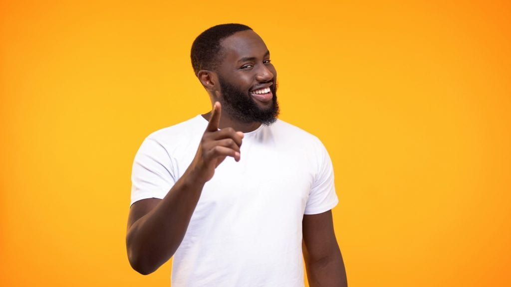 Smug Black man pointing finger camera and smiling yellow background.