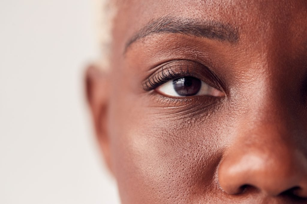 Close Up On Eyes Of Young Black Woman With Dyed Hair In Studio.