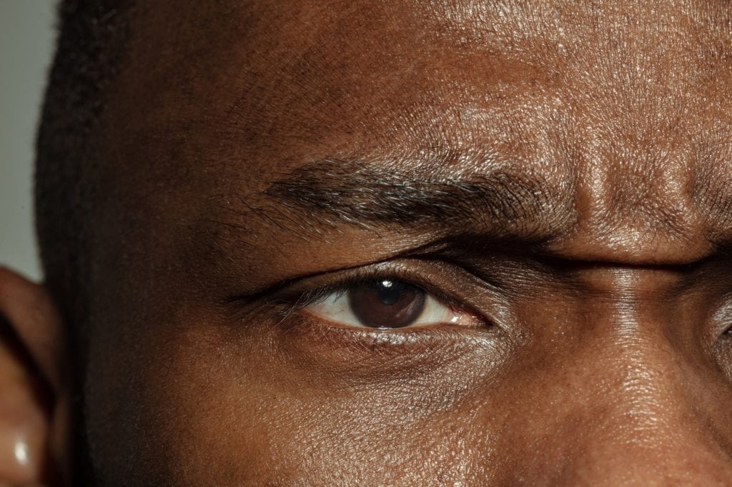Close up of face of young Black man, focus on eyes.