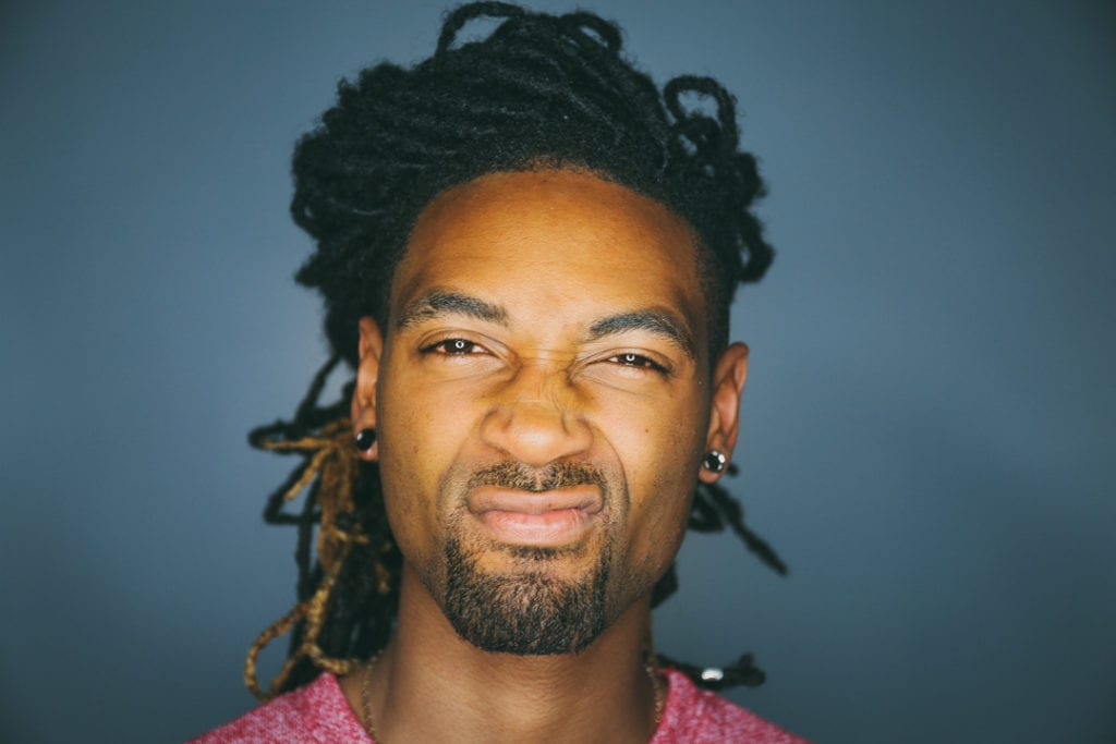 A close-up of a black man with locs and small gauge earrings staring disapprovingly at the camera.