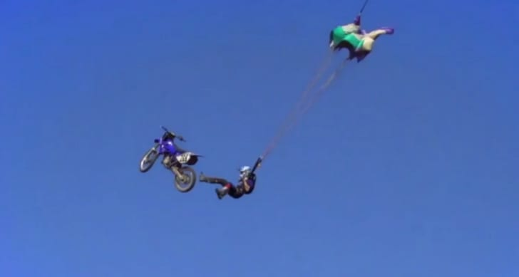 A person skydiving off of a motorcycle in the air with a parachute.