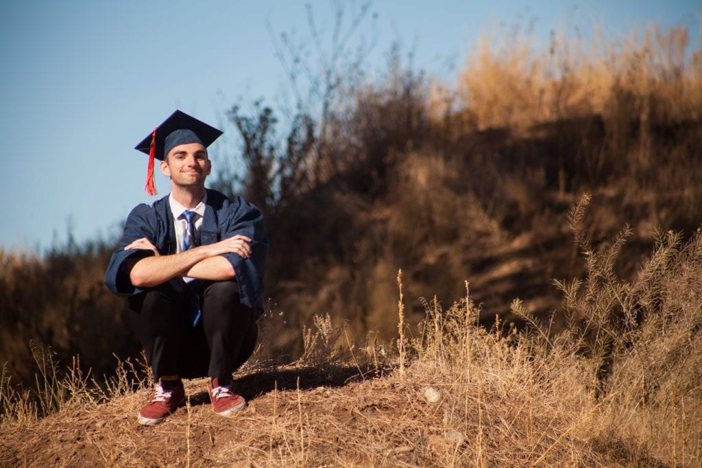 Young male in graduation robes and hat with red tassel and shoes