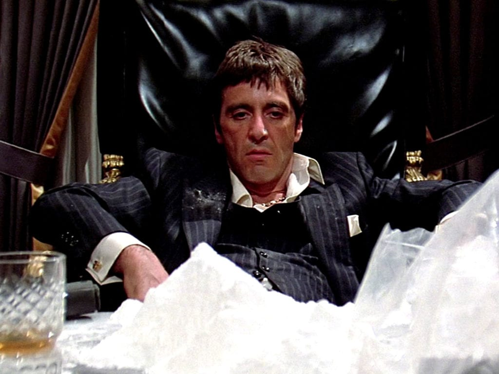 A scene from the movie Scarface where the main character is sitting at a desk that is covered in a large mountain of cocaine.
