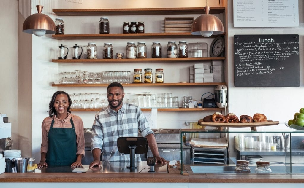 Portrait of two young African American entrepreneurs standing welcomingly together behind the counter of their trendy café.