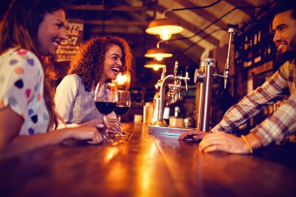 Young women interacting with bartender at counter in pub.