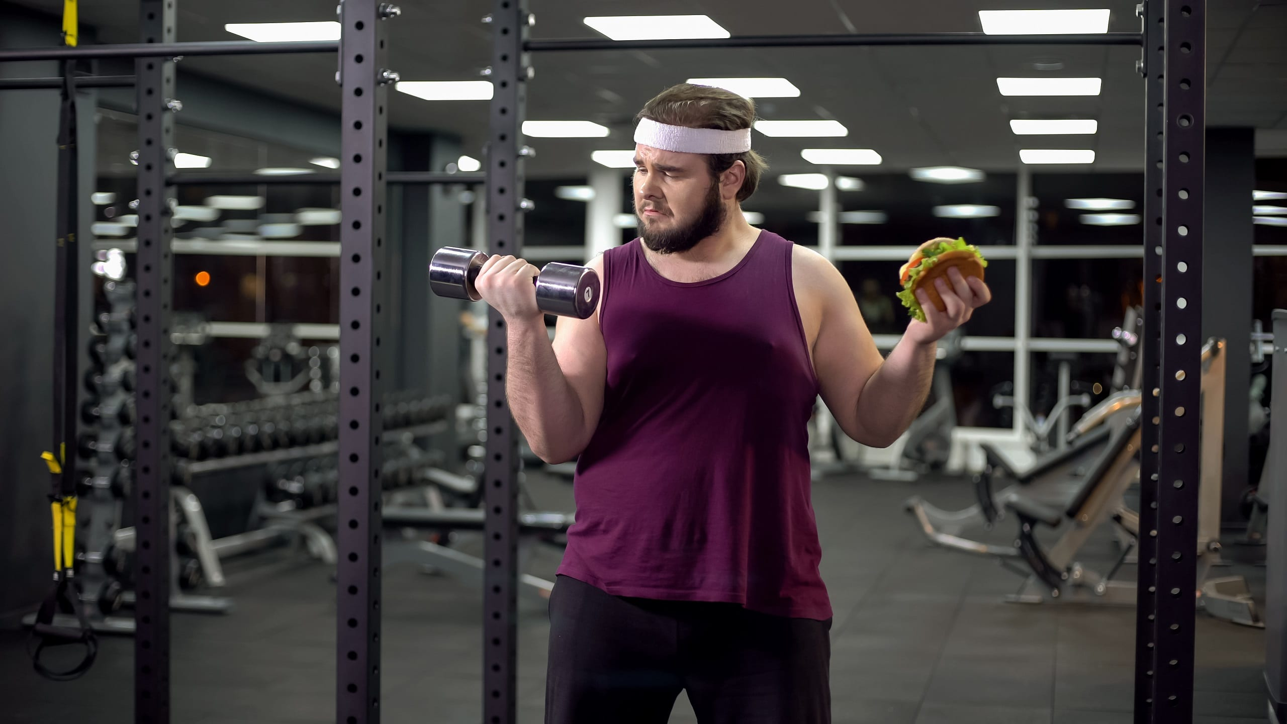 White male in the gym working out trying to get in shape choosing between sport and fast food, burger addiction and motivation. Choices and Self-Discipline.
