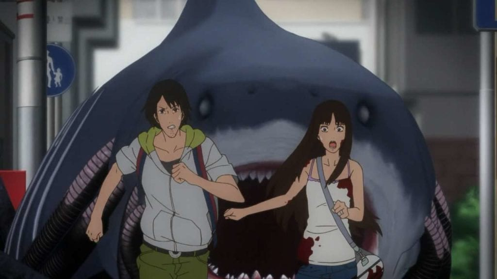 A scene of a shark attacking the main characters on land in GYO: Tokyo Fish Attack!